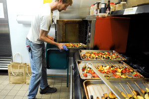Nick Schneider prepares roasted vegetable skewers for The Return of King Idomeneo: A Picnic Operetta, 2012